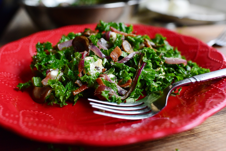 kale on a red plate with a fork